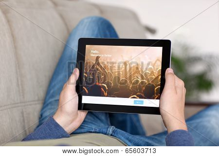 Man Lying On The Sofa And Holding Ipad With App Twitter On The Screen