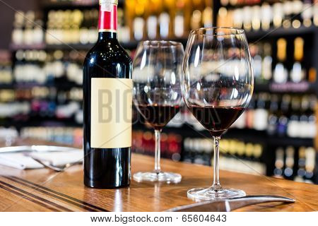Bottle of red wine and two glasses in wine shop