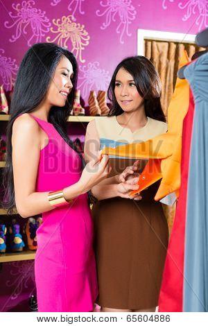 Asian young women choosing garment in fashion store