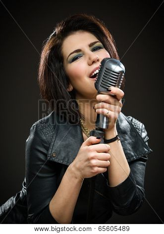 Half-length portrait of female rock singer wearing black jacket and keeping mike on grey background. Concept of music and rave