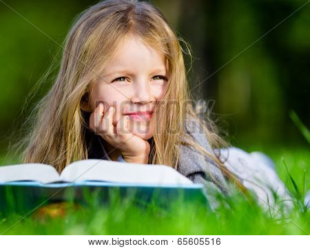 Pretty little girl reads interesting book lying on the green grass in the summer park