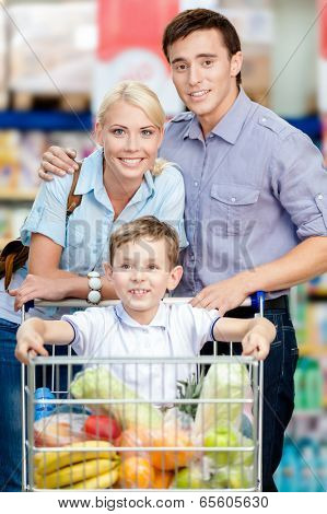 Family drives shopping trolley with food and son sitting there. Concept of fresh and healthy food and consumerism
