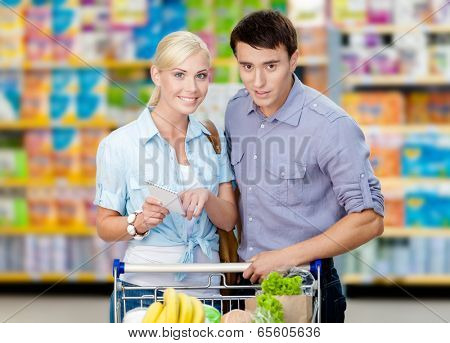 Happy couple discussing the shopping list and chosen products standing near the shopping trolley full of food