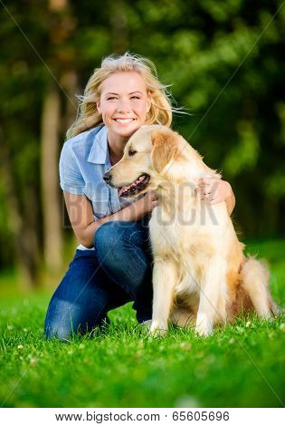 Woman with labrador sitting on the green grass in the summer park