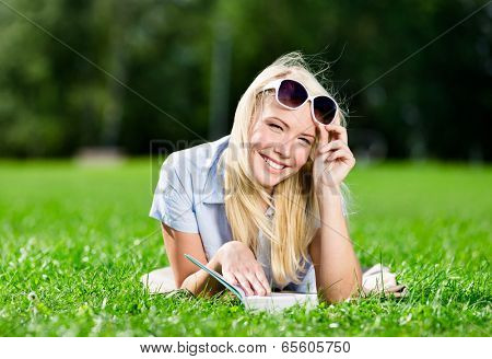 Girl in sunglasses reads the book lying on the grass