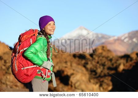 Active woman hiker living healthy lifestyle hiking outdoors wearing backpack smiling happy. Beautiful female trekking with looking with aspirations on Teide, Tenerife, Canary Islands, Spain,
