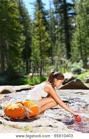 Hiking woman drinking water in river in Yosemite National Park after hiking. Happy girl smiling enjoying outdoors summer trekking vacation. Multicultural woman in California, USA.