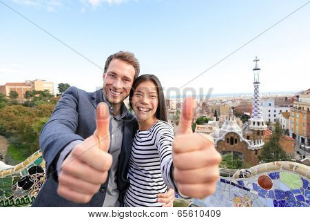 Travel couple happy in Park Guell, Barcelona, Spain. Beautiful young multiracial couple giving thumbs up hand sign smiling happy having fun on Europe vacation trip. Asian woman, Caucasian man.
