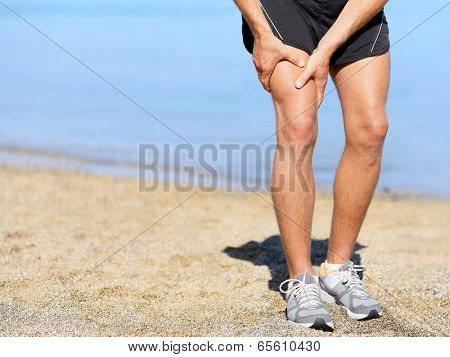 Muscle injury. Runner man with sprain thigh muscle. Athlete in sports shorts clutching his thigh muscles after pulling or straining them while jogging on the beach wearing running shoes.