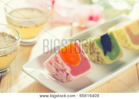 Colorful snow skin mooncakes on white plate with teacup. Chinese mid autumn festival foods.