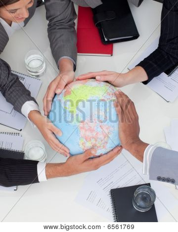 Close-up Of Multi-ethnic Business People Holding A Terrestrial Globe