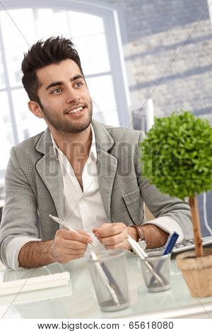 Happy young man sitting at desk, working in office.