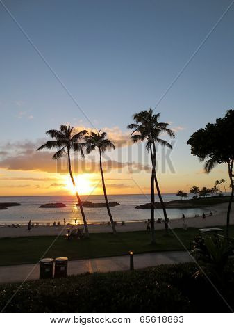 Sunsets On Ko Olina Lagoon Between Coconut Trees Over The Pacific Ocean As People Admire View