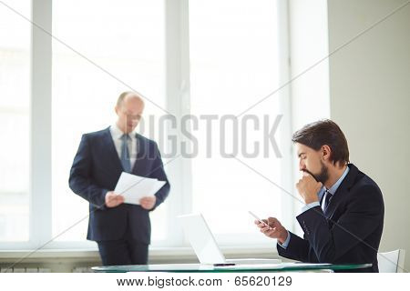 Image of handsome businessman using cellular phone at workplace with his colleague on background