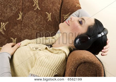 Woman Listen Music And Relaxing On Sofa