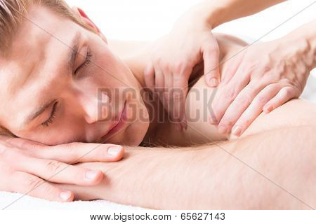 Handsome man lying in a spa salon enjoying a deep tissue back massage.