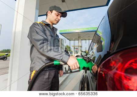 Gas station assistant refueling a car