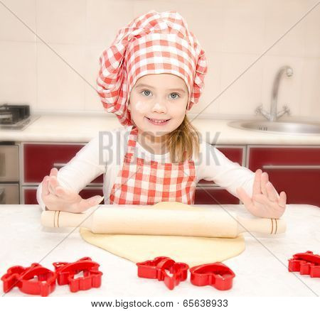 Smiling Little Girl With Chef Hat Rolling Dough