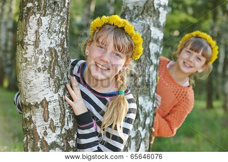 two laughing sister girls outdoors in birch forest