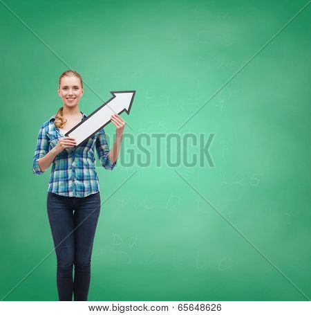 happiness, direction and people concept - smiling young woman arrow poiting up on green board background
