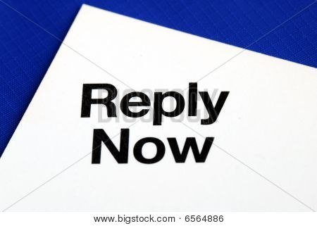"""Reply Now"" from a business reply postcard isolated on blue"