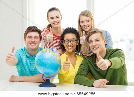 education, travel and geography concept - five smiling student with earth globe at school showing thumbs up