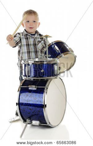 A young preschooler trying to catch the rhythm on his drum set.  On a white background.