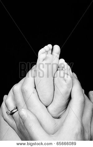 Mother holds the feet of her newborn son. Black and white with space for your text.