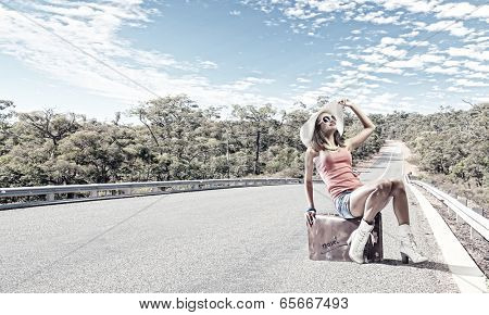 Young pretty girl traveler sitting on suitcase aside of road