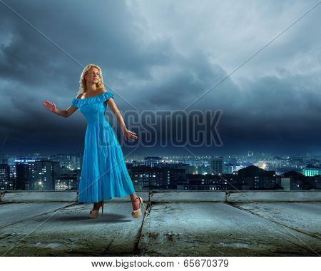 Anxious young woman in blue dress looking back worried