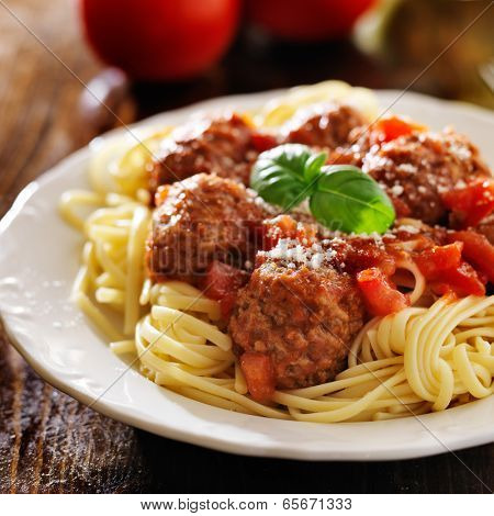 spaghetti and meatballs with basil garnish
