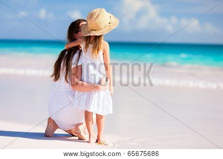 Back view of mother and daughter at Caribbean beach enjoying summer vacation