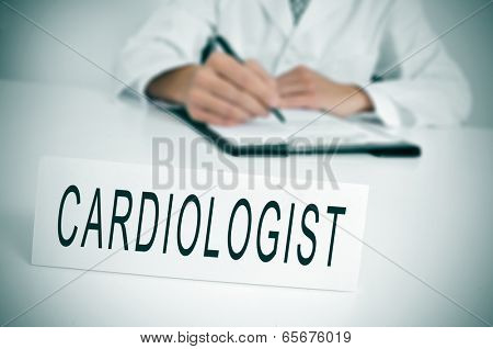 a doctor sitting in the desk of his consulting room writing in a clipboard and a nameplate with the word cardiologist written in it