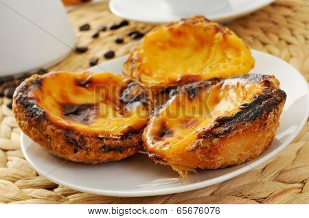 a plate with pasteis de nata, typical Portuguese egg tart pastries on a set table