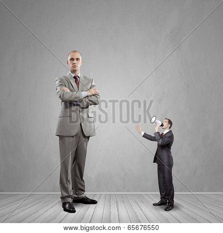 Big bossy businessman looking down at small businessman