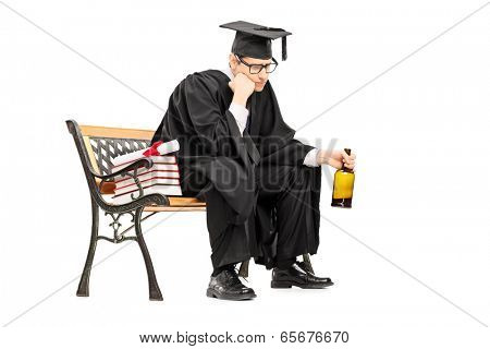 Sad college graduate drinking alcohol seated on bench isolated on white background