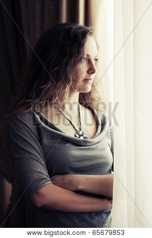 Sad beautiful woman with long curly hairs looking out the window