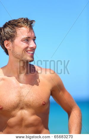 Handsome good-looking man on beach smiling happy after swimming during vacation in holiday resort. Male model enjoying sunny holidays under the sun. Young Caucasian man in his twenties.