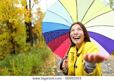 Umbrella woman in Autumn excited under rain on fall day.Beautiful young female wearing raincoat surprised and excited in the rain. Mixed race Asian Caucasian girl in her 20s walking in forest.
