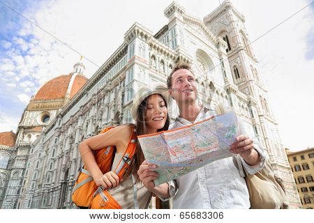 Tourist travel couple by Florence cathedral, Italy looking at map in front of Il Duomo di Firenze also called Basilica di Santa Maria del Fiore. Main tourist attraction and landmark in Florence, Italy