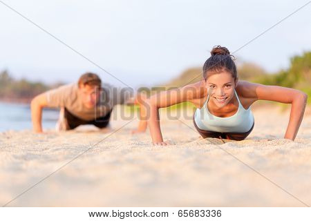 Fitness young people doing pushups on beach. Fit couple, female sport model and man training crossfi