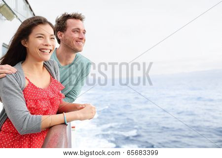 Cruise ship couple romantic on boat looking at view in romance. Happy lovers, woman and man traveling on vacation travel sailing on open sea ocean. Young Asian woman and Caucasian man.