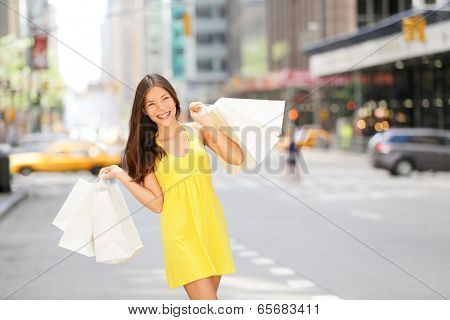 Urban shopping woman in New York City street with yellow taxi cab. Beautiful happy summer shopper ho poster