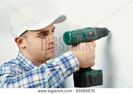 Man With Drill Making Hole In Wall