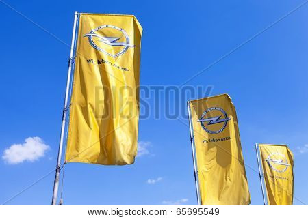 Samara, Russia - May 25, 2014: The Flags Of Opel Over Blue Sky. Opel Is A German Automobile Manufact