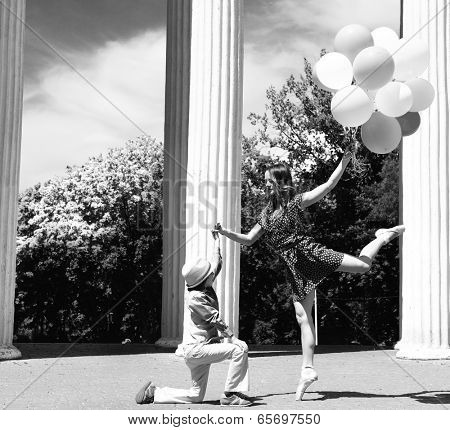 Elegant beautiful teen girl dancer in pointes posing outdoor with little boy holding colored balloons. Black and white.