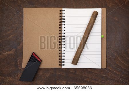 Opened notebook cigar and matches.