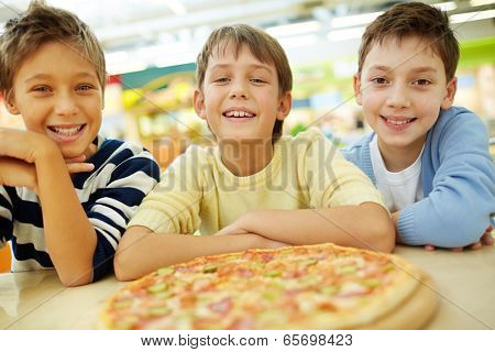 Three boys thrilled with pizza looking at camera