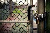 stock photo of eyeleteer  - Closeup of a locked padlock securing a metal chain - JPG