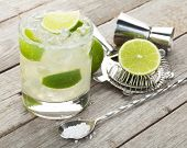 pic of lime  - Classic margarita cocktail with salty rim on wooden table with limes and drink utensils - JPG